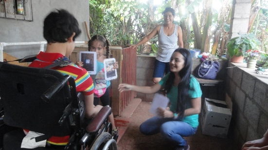 This photo shows a young woman providing instruction to two children. One child holds an image on a screen and shows it to a young boy who uses a wheel chair.